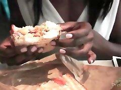 Black girl enjoys a sandwich at a restaurant