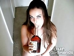 Brunette sucks on a bottle of Hennessy